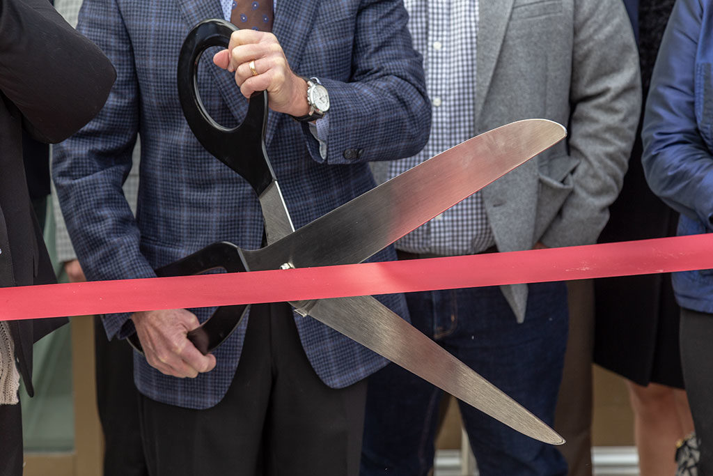 A man with a blue plaid sport jacket holding an oversized pair of scissors cutting red ribbon.