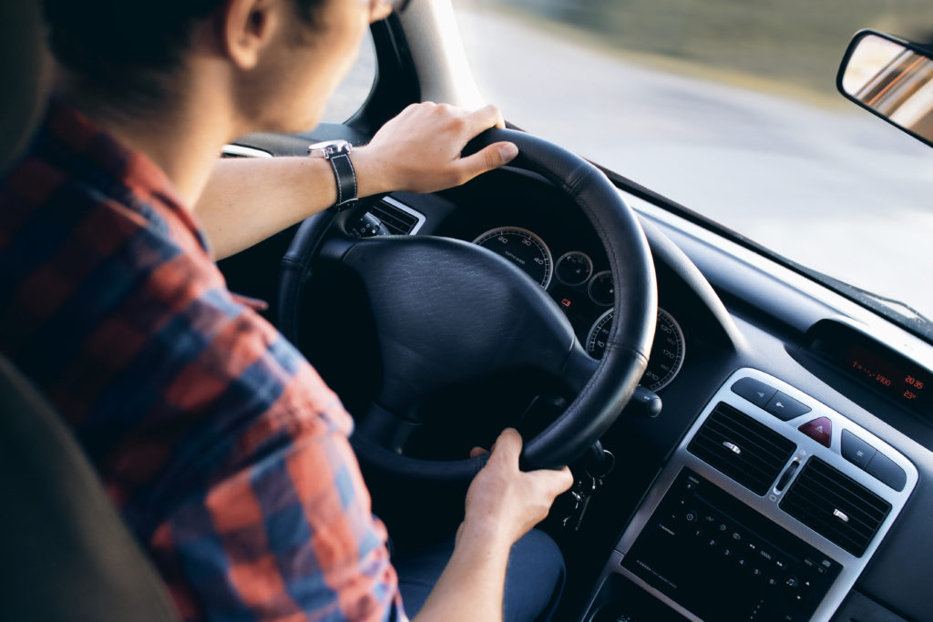 Over the shoulder view of a man wearing a plaid shirt with hands on the wheel