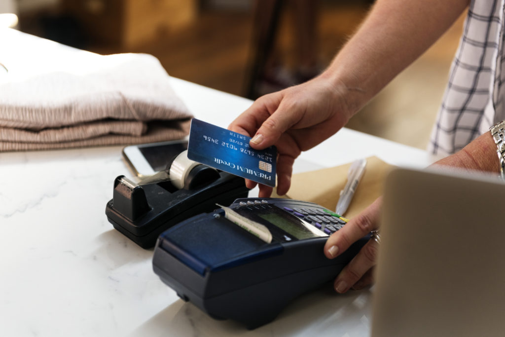 A person holding a blue credit card in the process of charging a purchase to it