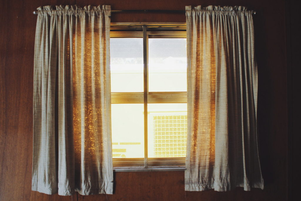 Window with partially open grey drapes on a sunny day