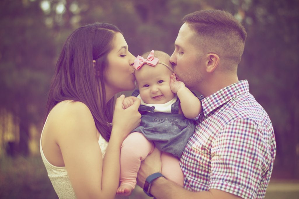 Young mother and father holding their daughter between them whilst kissing her.