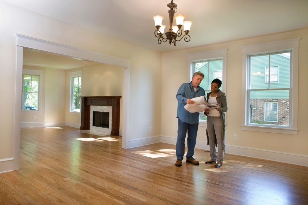 A man and a woman discuss blueprints in an open unfurnished house.