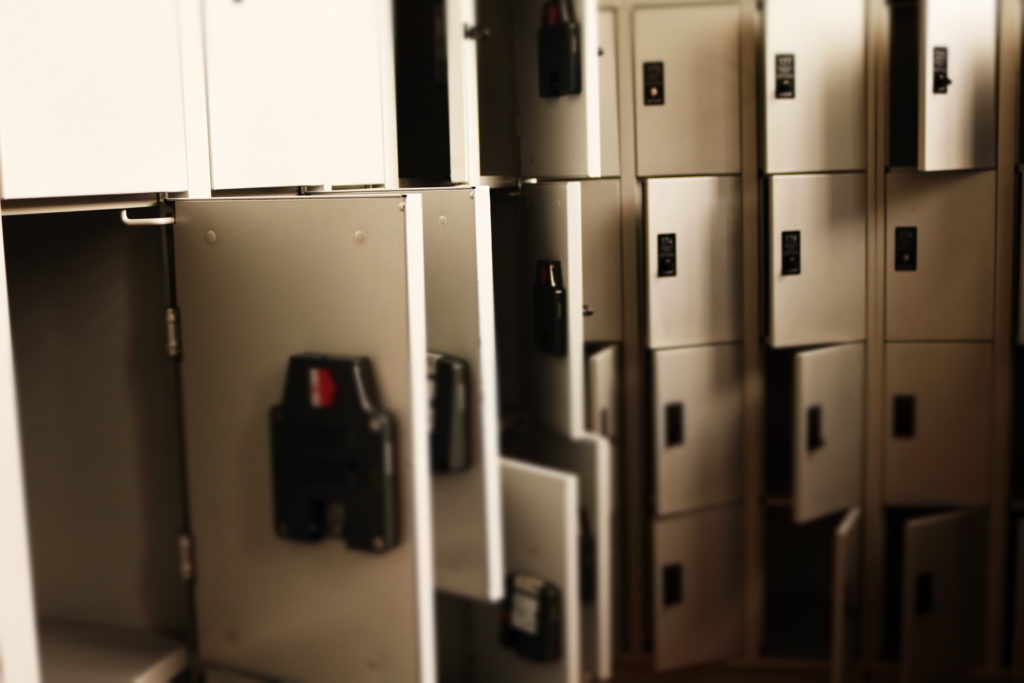 A wall of off-white lockers with some of the doors open and some closed.