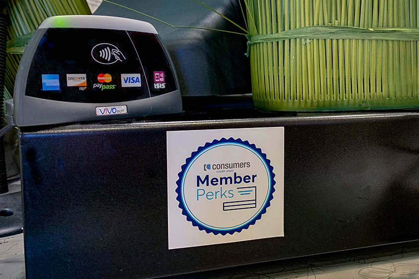 A Consumers Credit Union Member Perks on a cash register in a retail setting.