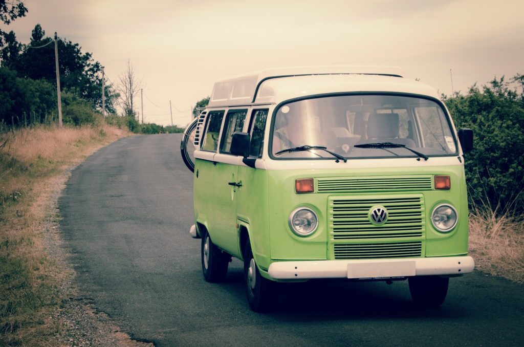 A lime green Volkswagen bus driving around a curve on a country road.