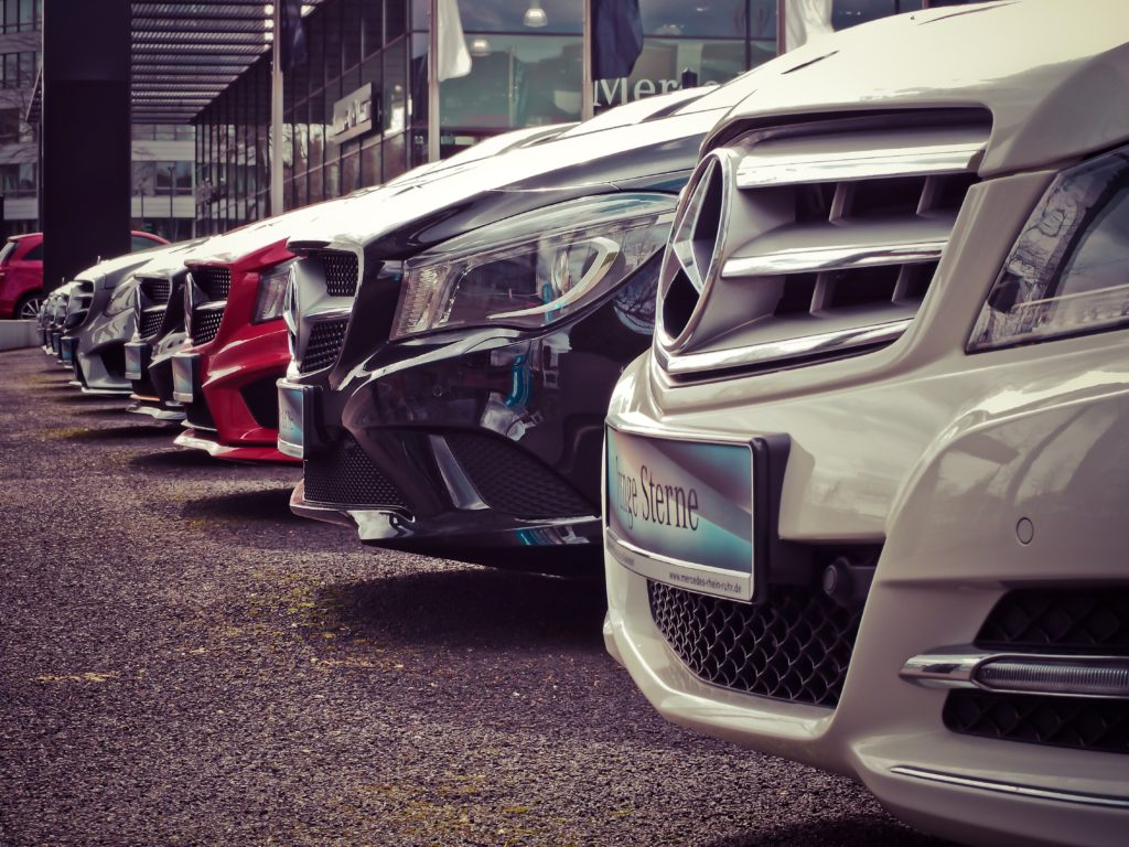 A line of Mercedes cars' front ends in a car dealership parking lot.