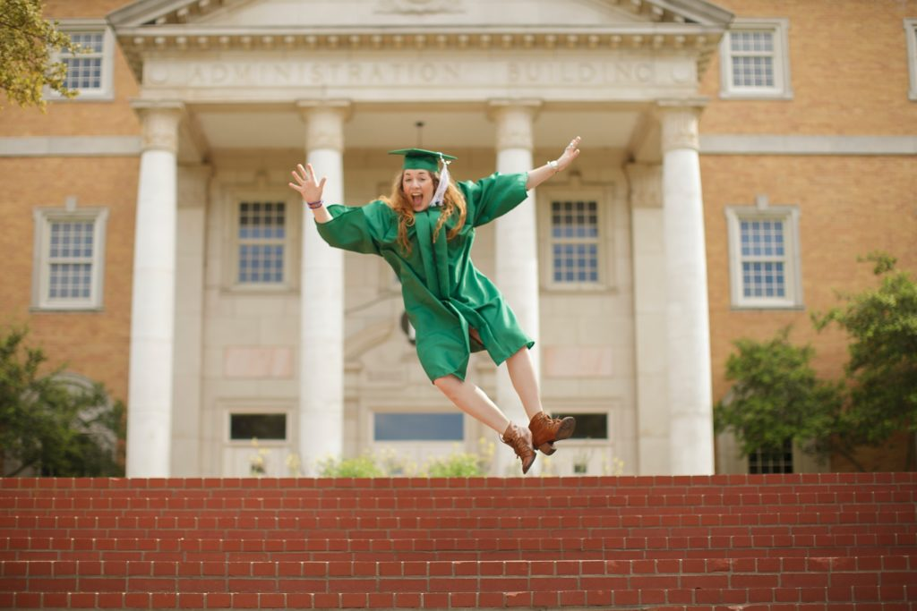 Female graduate jumping excitedly