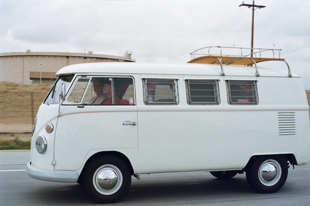 A white classic Volkswagen bus driving on an overcast day.