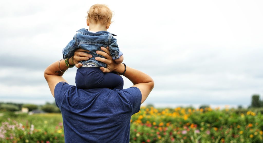 Father holding small child on his shoulders
