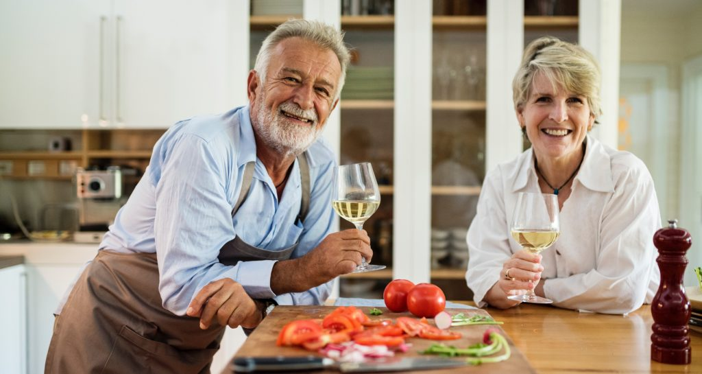 Married couple holding glasses of white wine over a island countertop with a cutting board covered with chopped vegetables.