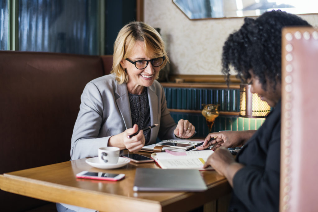 Two women sitting a booth referring to their agendas while enjoying coffee.
