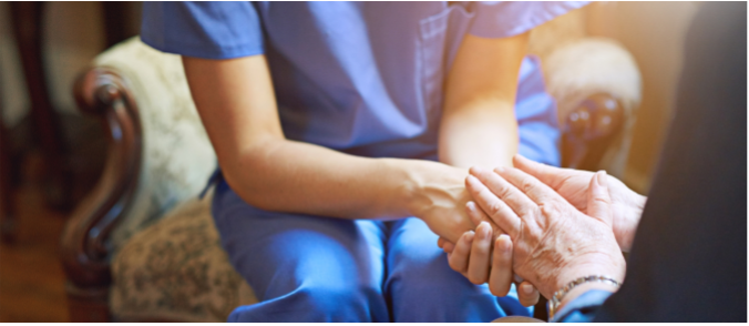 A healthcare provider wearing scrubs holding hands with an elderly person.