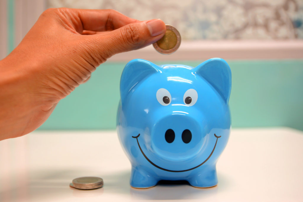 A hand placing British currency into a blue piggy bank.