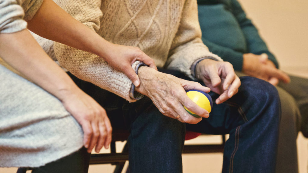A woman holding an elderly man's hand that is holding a colorful ball.
