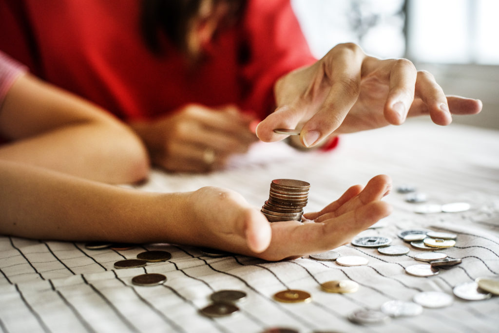 A person holds a stack of coins in their hand