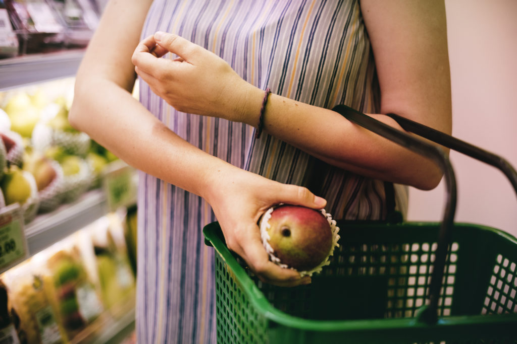 Woman putting red apple into a green shopping basket