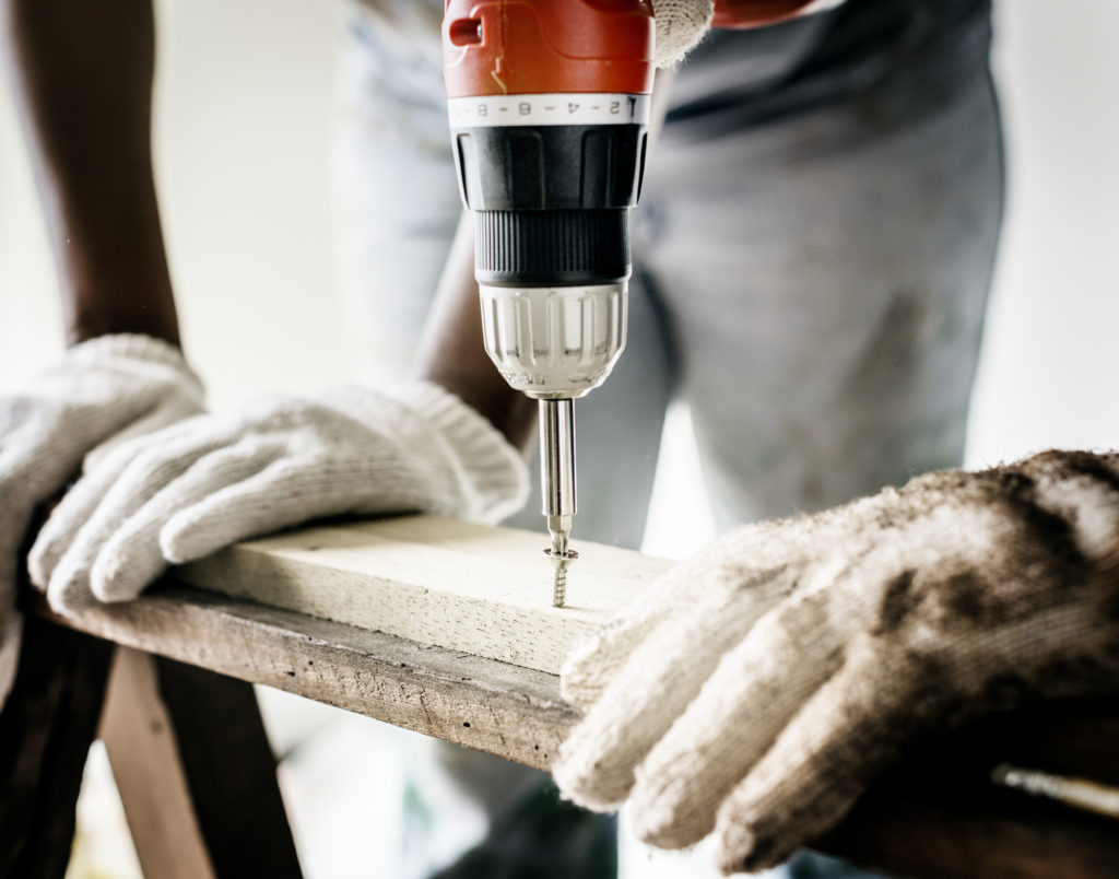 Repairman wearing white gloves drilling screw into wood plank