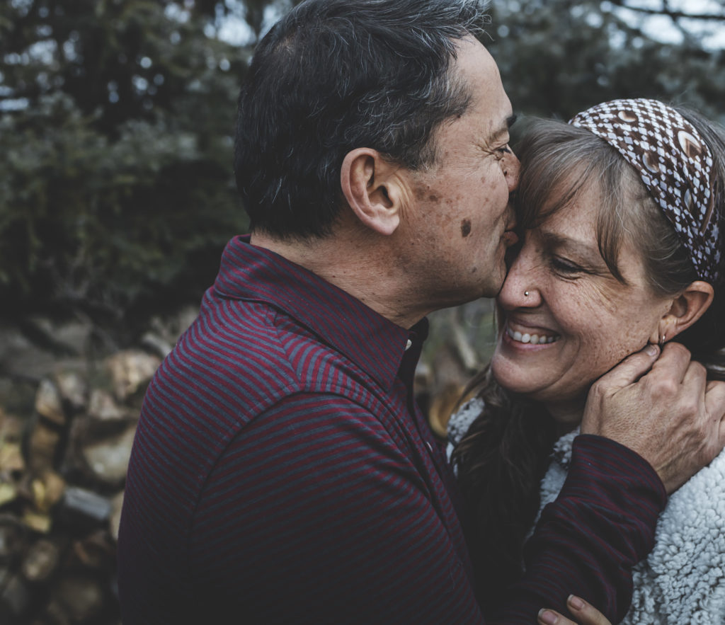 Mature couple embraces as husband kisses his smiling wife on her forehead
