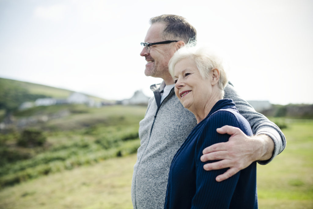 Smiling man with his arm wrapped around a woman's left shoulder