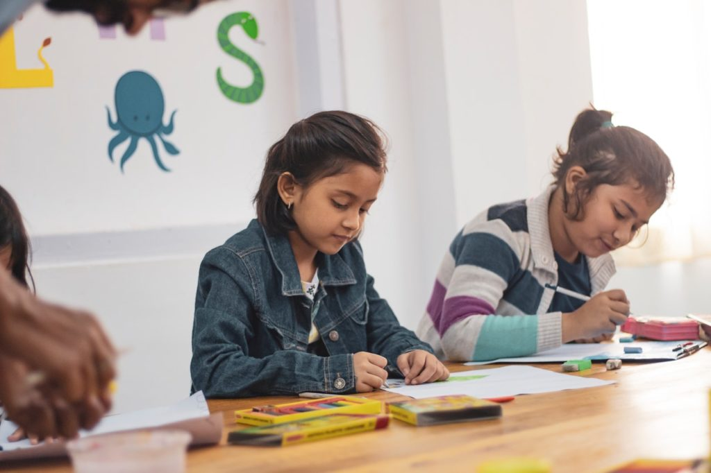 two girls sit in a classroom doing work