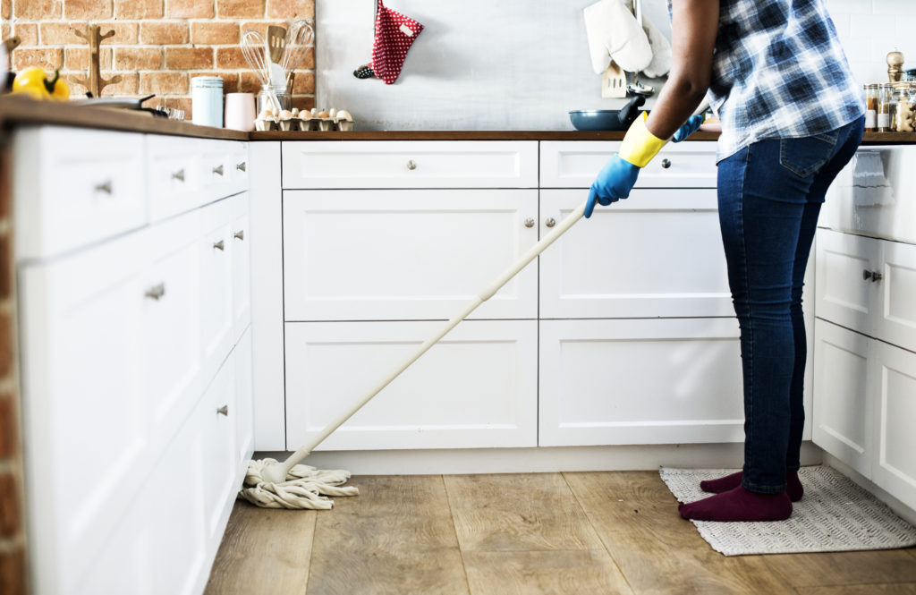 Person wearing gloves mopping a kitchen floor