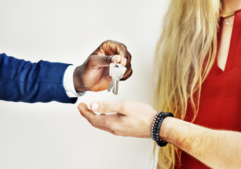 Business man putting keys into the hand of a woman wearing a red shirt