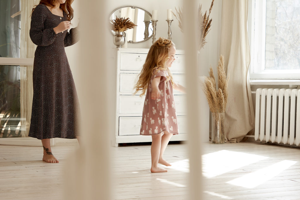 Woman walking behind toddler in a room