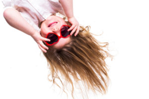 A girl with long brown hair with red heart-shaped sunglasses hanging upside down.