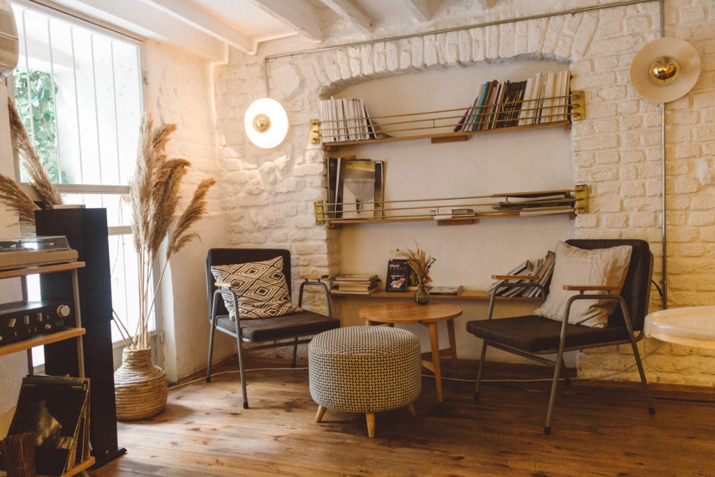 Reading corner with a with chairs and shelves against a white brick wall