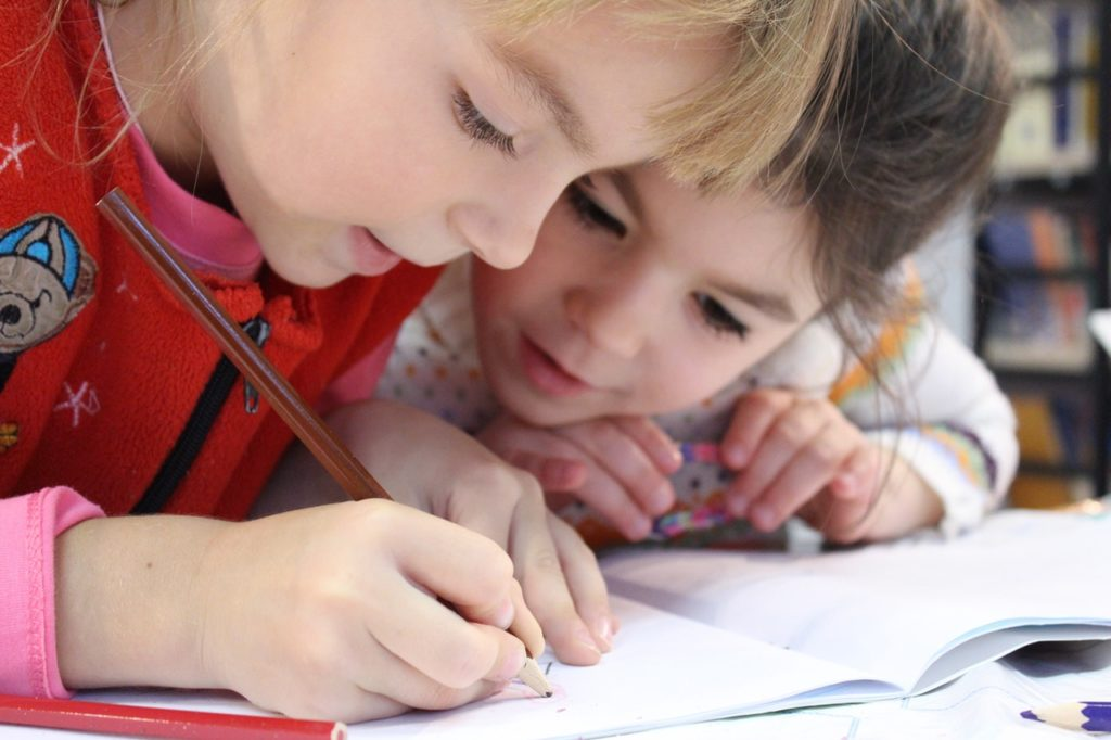 children drawing in a book