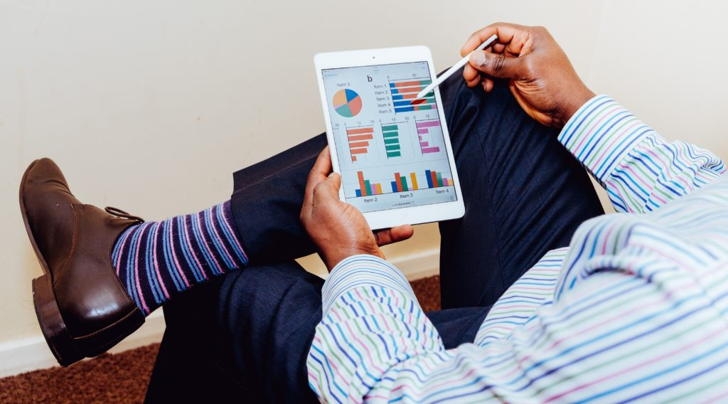 A man wearing colorful striped shirt and socks looking graphs on a tablet.