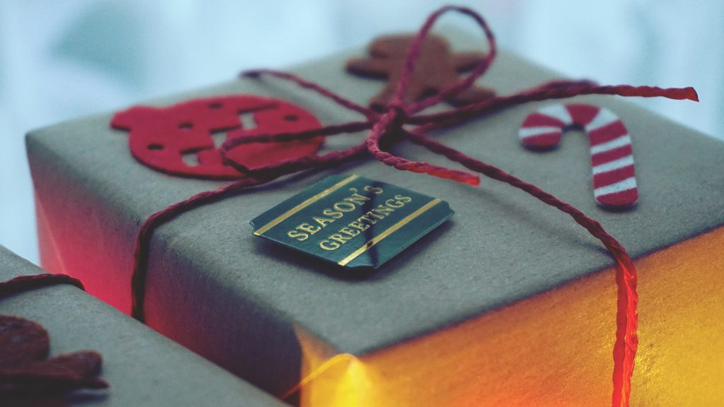 Close up photo of a wrapped gift tied with a red bow