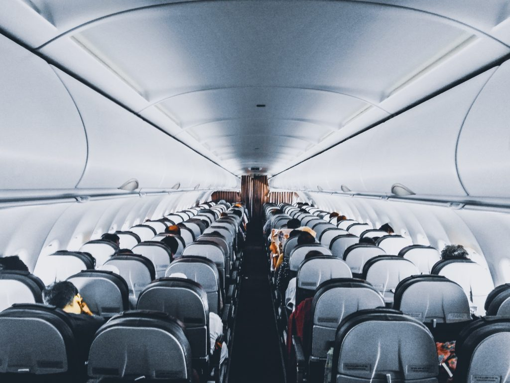Overhead view from the back of passengers inside a commercial airplane