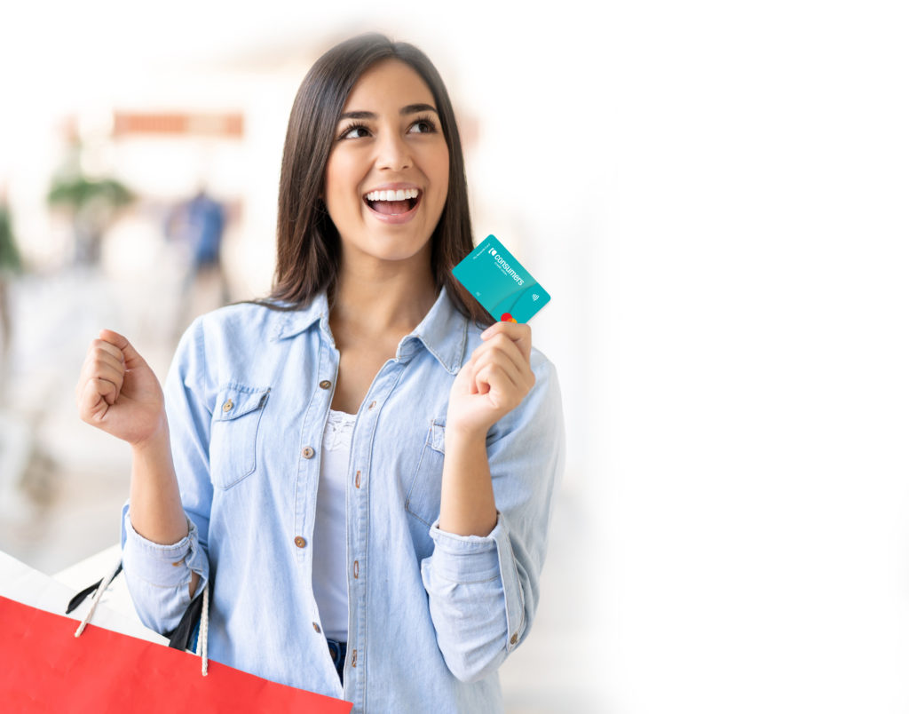 Excited young woman looking away daydreaming while holding her debit card and shopping bags