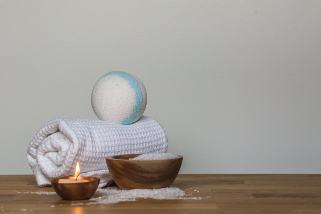 Photo of a white towel and bath bomb next to a candle