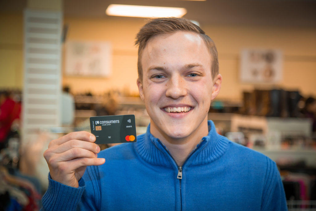 A blonde young man wearing a blue sweater holding a black Consumers Credit Union debit card.