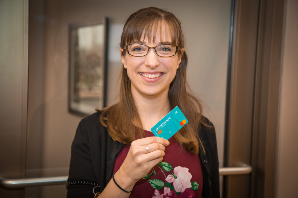 A woman with glasses and a cardigan holding a blue Consumers Credit Union Rewards card.