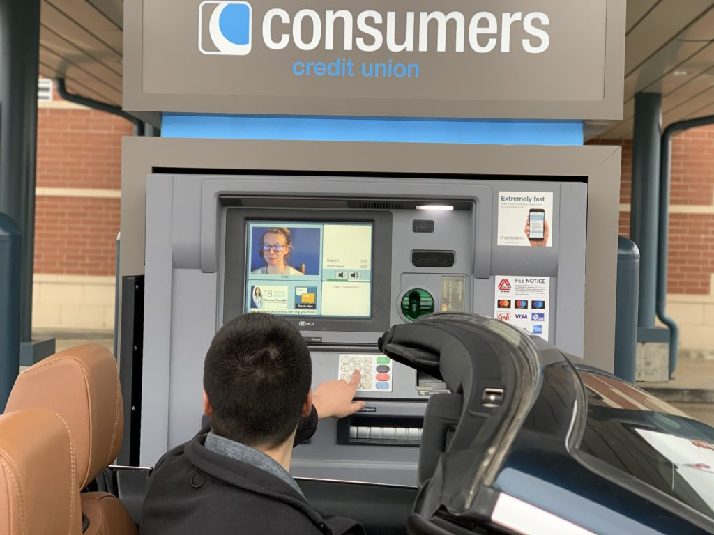 A man in a convertible banking with a TellerPlus Interactive Teller at a Consumers Credit Union.