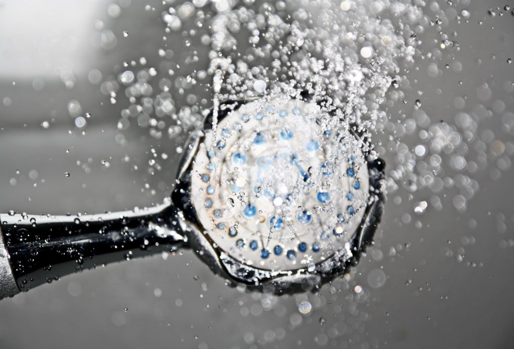 Black shower head switched on with water coming out