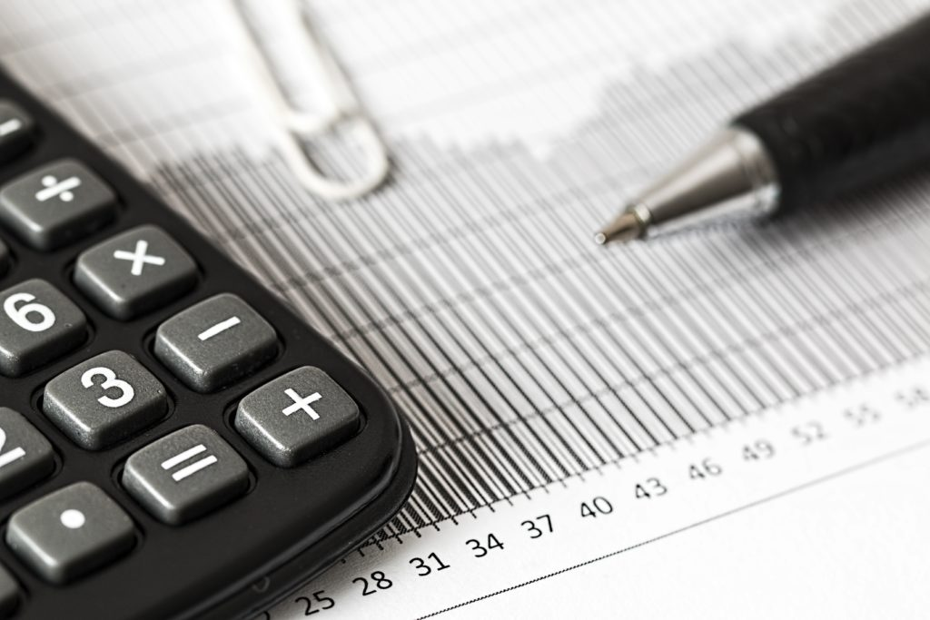 Calculator and pen on a table with financial documents