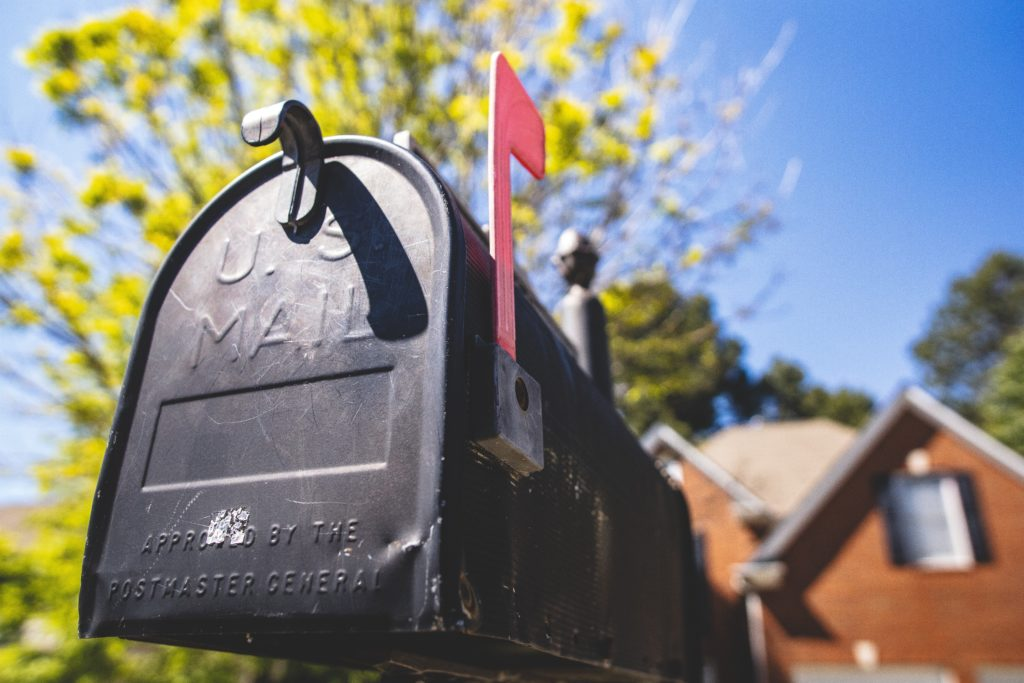 Up close of black mailbox with red flag