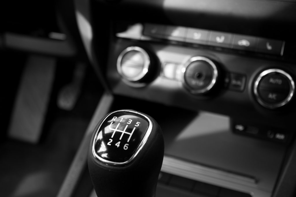 A manual stick shift in a car with black interior.