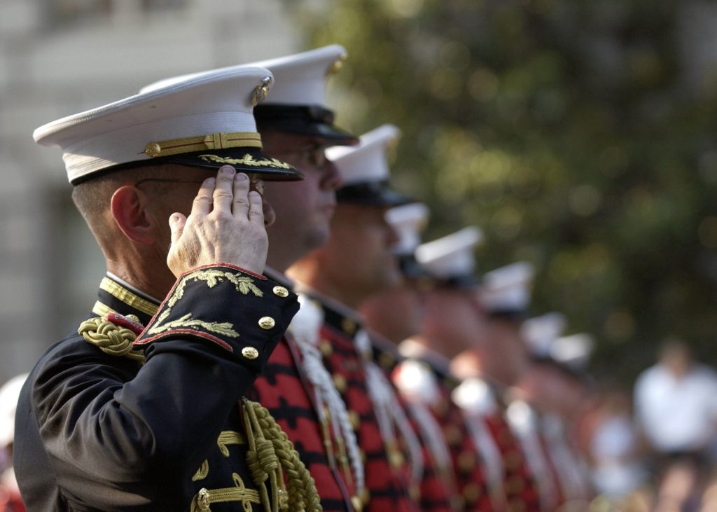 Military personnel in a line saluting