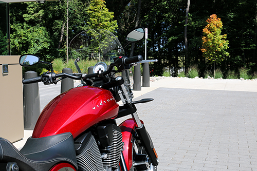 Red motorcycle parked near building by trees.
