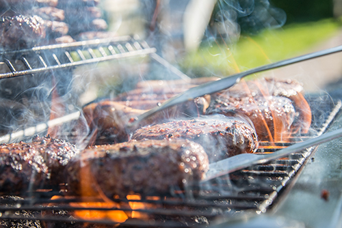 Close up photo of a turner turning over meat on a grill