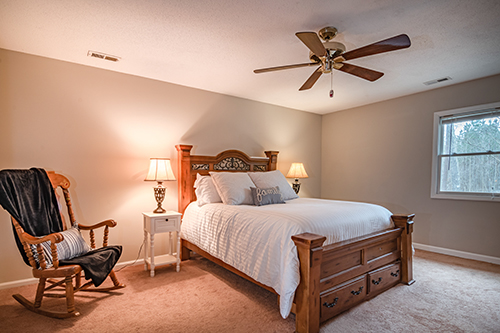 Bedroom with white linen and ceiling fan