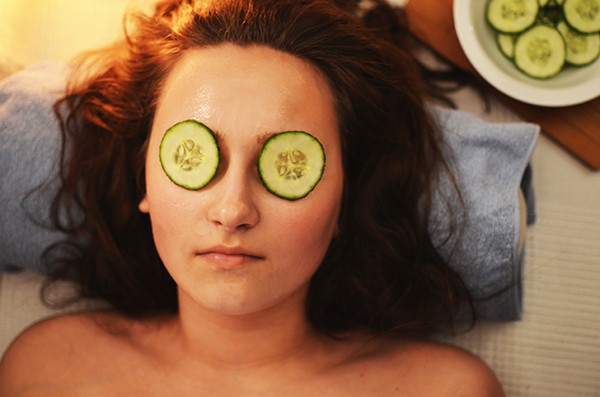 Woman at spa with cucumbers over her eyes