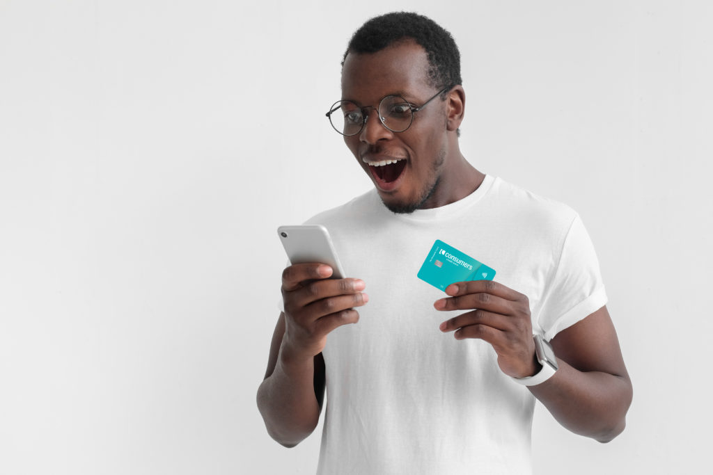 Excited black man wearing white shirt looking at his mobile phone