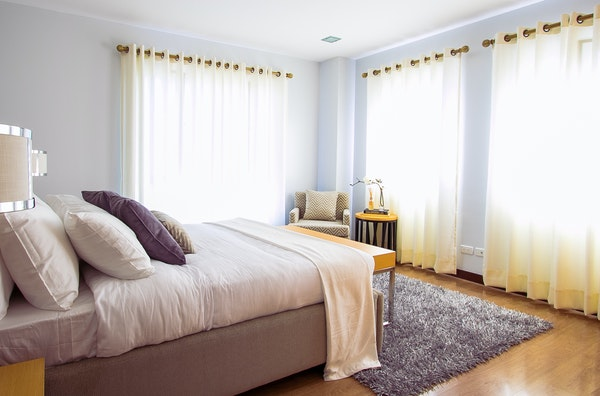 Gray bedroom set with gray area rug on a wood floor