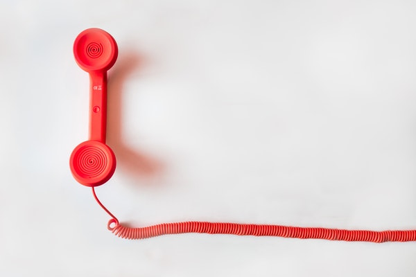 Red phone handset with red spiral cord against a white background